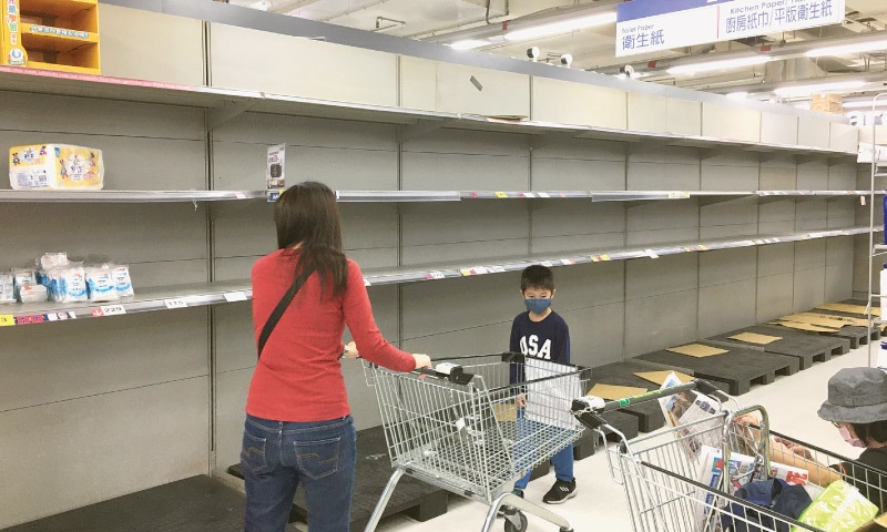 Taipei: Customers wearing face masks are seen next to empty shelves of toilet and kitchen paper section at a Carrefour supermarket, following the novel coronavirus disease (COVID-19) outbreak on Sunday.—Reuters