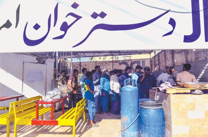 A LARGE number of people, mainly labourers and daily-wage earners, are lined up at one of the free eateries set up by a welfare organisation. —Fahim Siddiqi / White Star