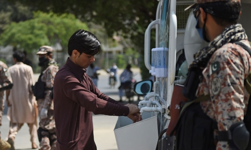 Pakistani rangers wearing face masks stand guard next to a man washing his hands during an awareness campaign amid concerns over the spread of the novel coronavirus, in Karachi on March 21. — AFP