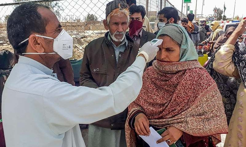 A health worker checks the body temperature of a pilgrim returning from Iran via the Pakistan-Iran border town of Taftan on February 29. — AFP