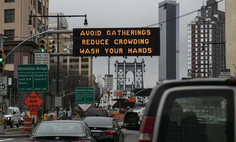 In this March 19, 2020 photo, the Manhattan bridge is seen in the background of a flashing sign urging commuters to avoid gatherings, reduce crowding and to wash hands in the Brooklyn borough of New York. — AP