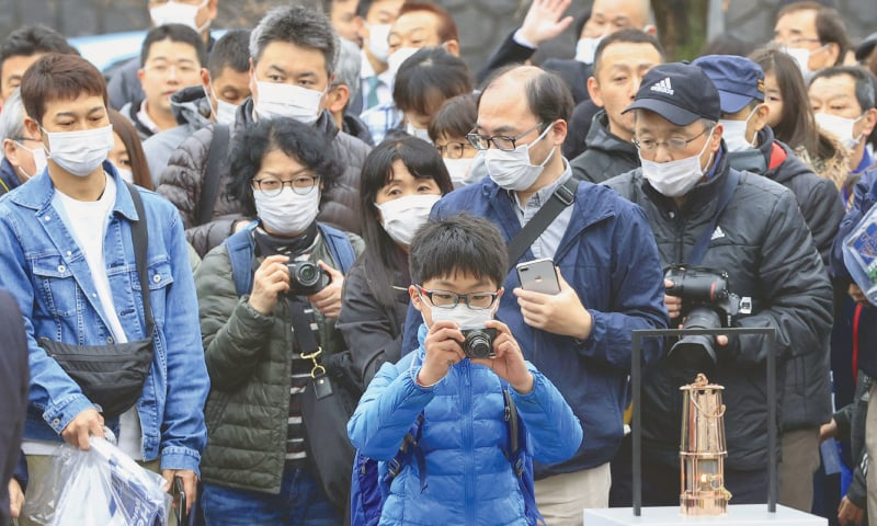 KAMAISHI: People wearing protective face masks following an outbreak of the coronavirus disease queue as they try to watch and take photos of the Olympic flame during the Tokyo 2020 Olympics Flame of Recovery tour at Kamaishi Station on Sunday.—Reuters