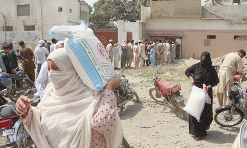 TWO women take away bags of flour while other people queue up for the essential commodity at a Korangi mill on Sunday. —Online