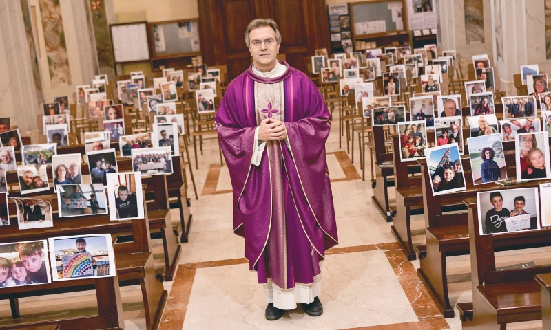 ROME: Don Giuseppe Corbari, parson of the Church of Robbiano, leads Sunday mass prayers with photographs sent in by his congregation members and glued to empty pews due to a nationwide lockdown.—AFP