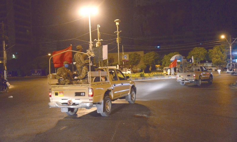 KARACHI: Army vehicles patrol near Governor House after Sunday midnight.—Shakil Adil / White Star