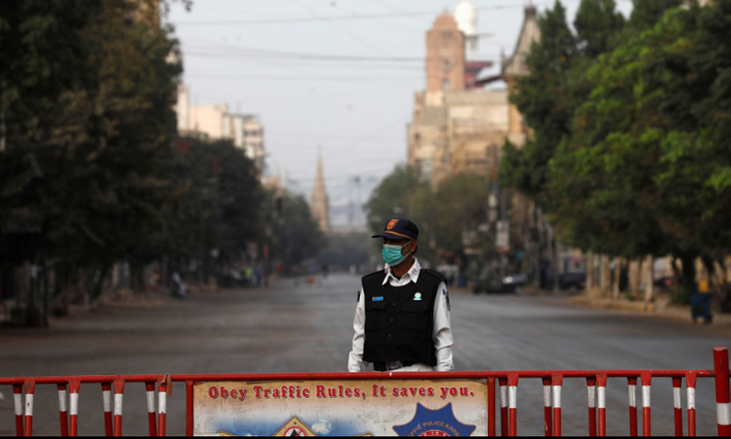 A traffic police officer stands with a barrier on a deserted road of a business district during a partial lockdown after Pakistan shut all markets, public places and discouraged large gatherings amid an outbreak of coronavirus disease in Karachi on March 23. — Reuters