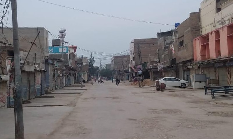 A few vehicles are seen on an otherwise deserted road in Jacobabad. — photo provided by Azhar Gul Sarki