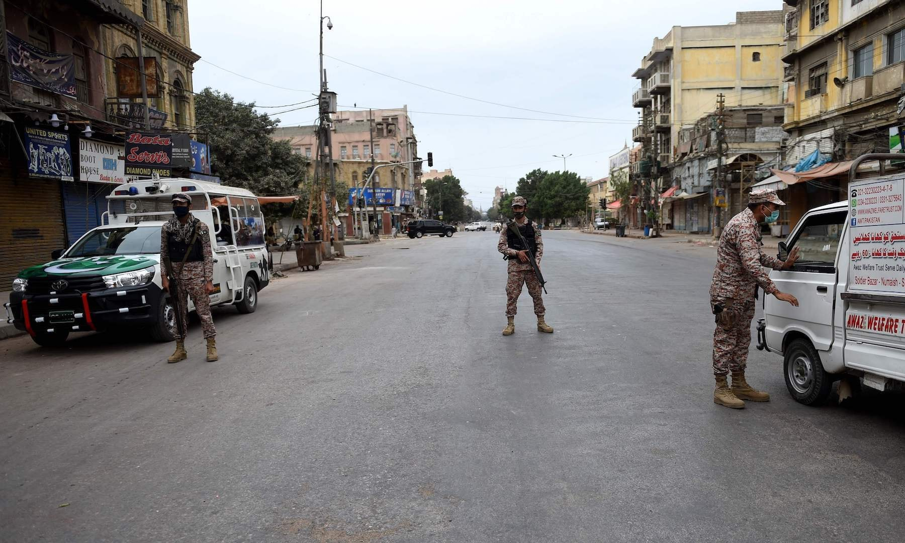 Soldiers wearing facemasks stand guard on a deserted street during a lockdown in Karachi on March 23. — AFP