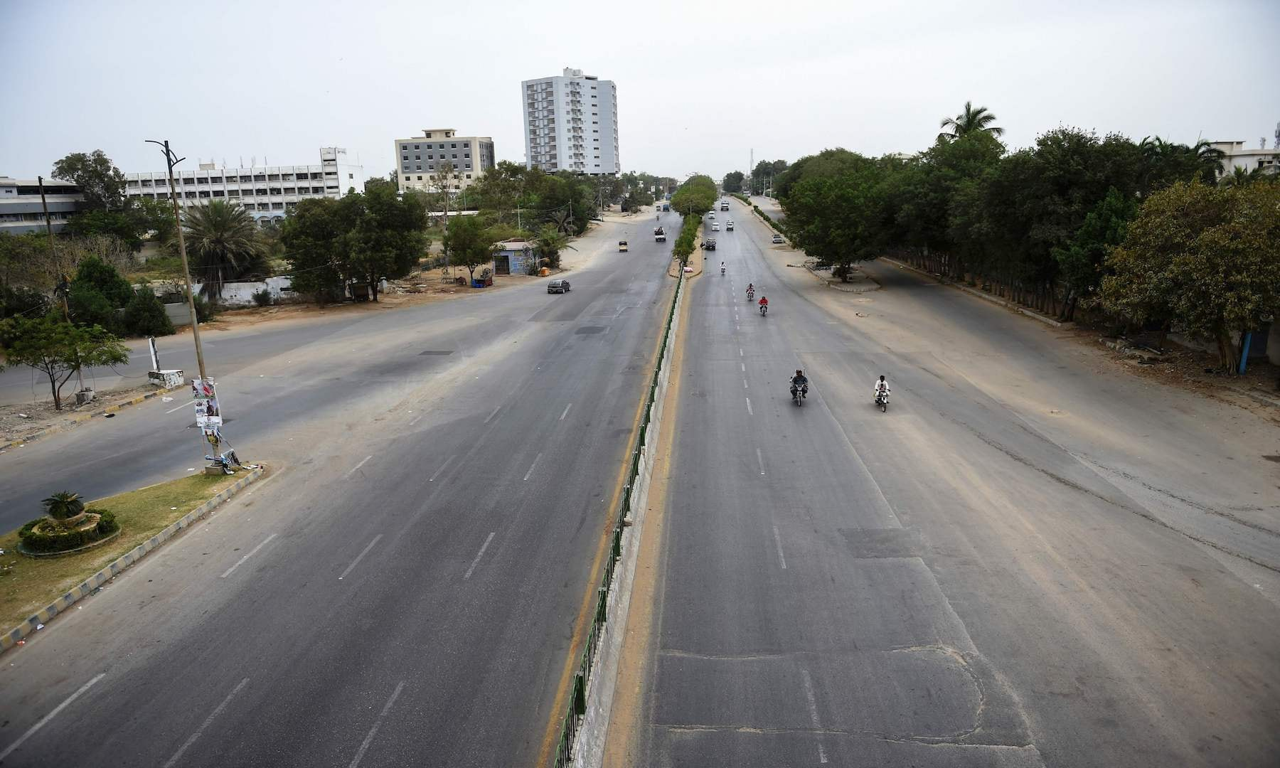 Commuters ride on a deserted road during a lockdown in Karachi on Monday. — AFP