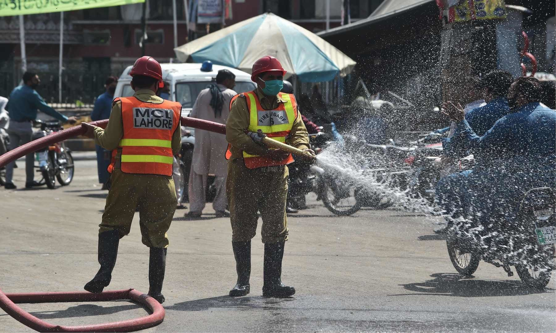 Municipals workers spray a solution to disinfect a street in a closed market area during a lockdown in Lahore's old city. — AFP