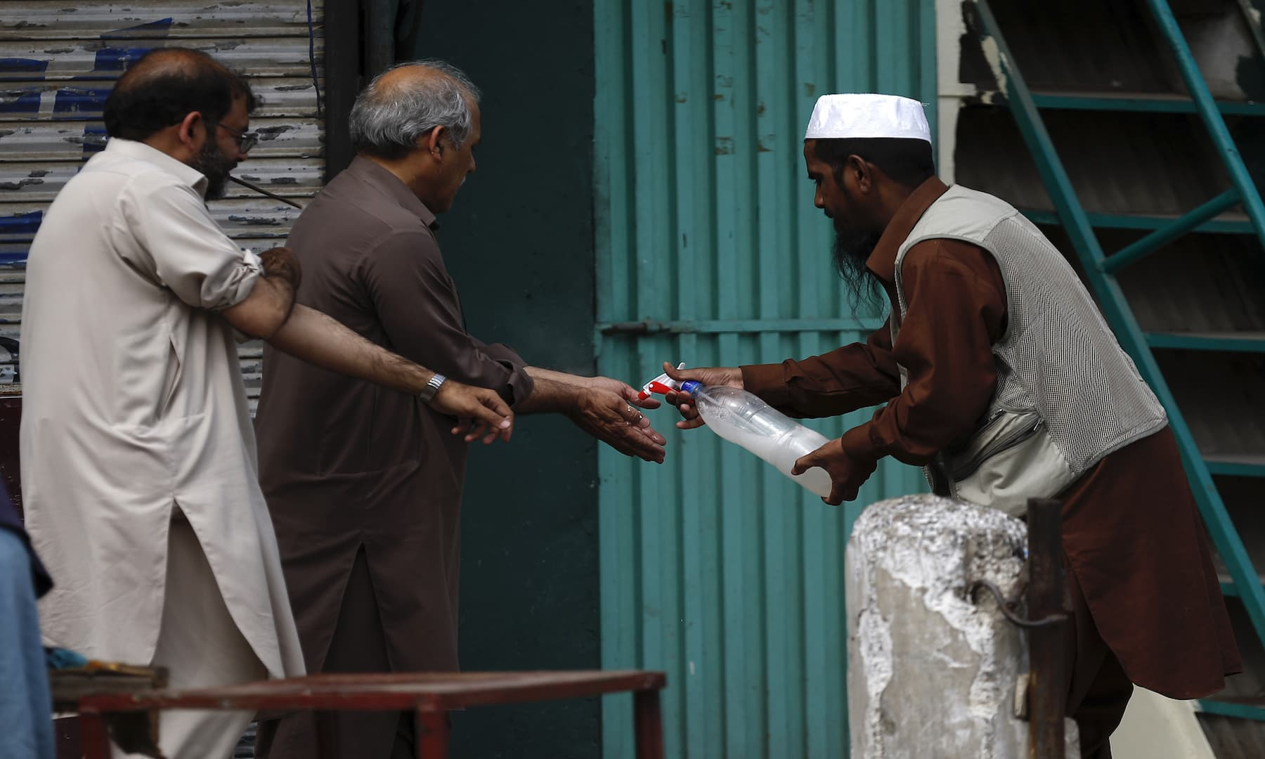 A volunteer sprays disinfectant on the hands of worshippers to help curb the spread of coronavirus outside a mosque in Rawalpindi on Monday. — AP