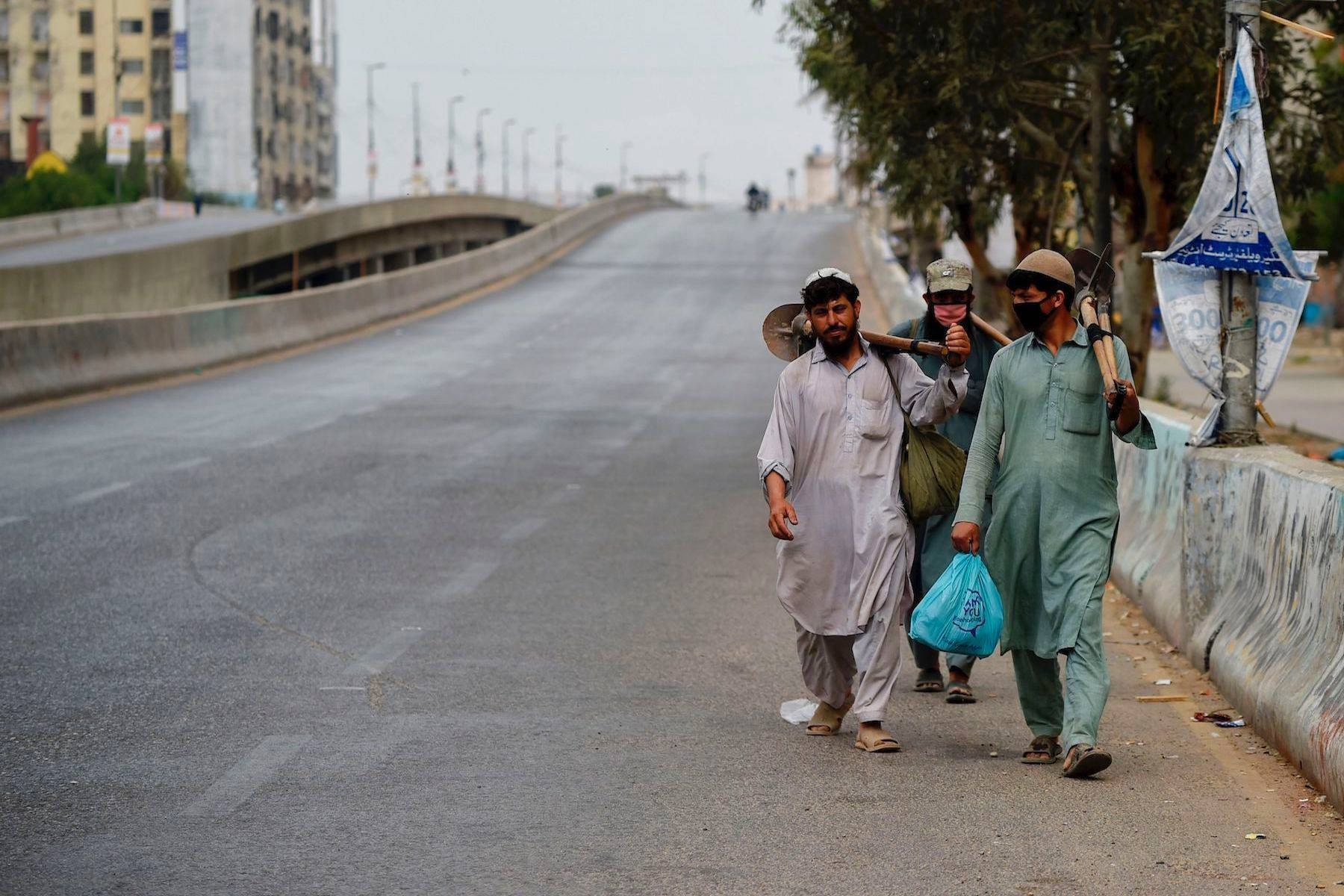 Labourers walk on a deserted street during a lockdown in Karachi. — AFP