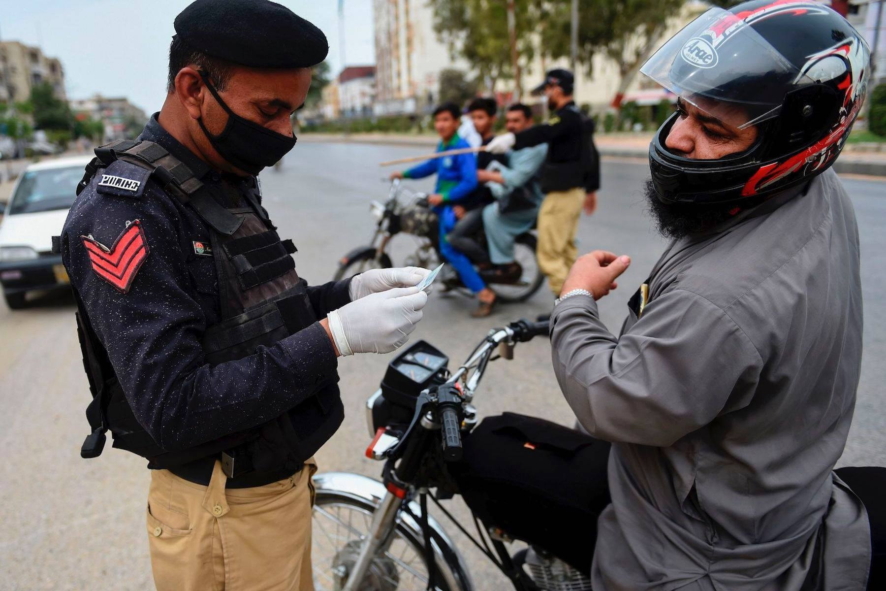 A policeman checks the identity card of a motorcyclist during a lockdown in Karachi. — AFP
