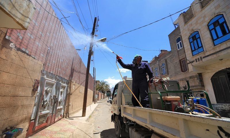 A government worker who is part of a combined taskforce tackling the coronavirus sprays disinfectant in a neighbourhood as part of safety precautions, in Yemen's capital, Sanaa, on March 23, 2020. — AFP