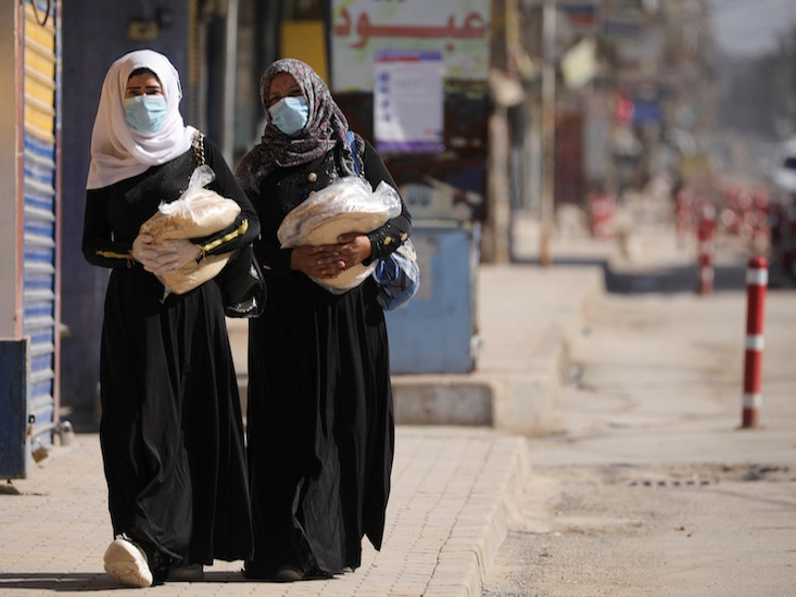 Women hold stacks of bread as they walk along an empty street, as restrictions are imposed as measure to prevent the spread of the coronavirus disease in Qamishli, Syria, on March 23, 2020. — Reuters