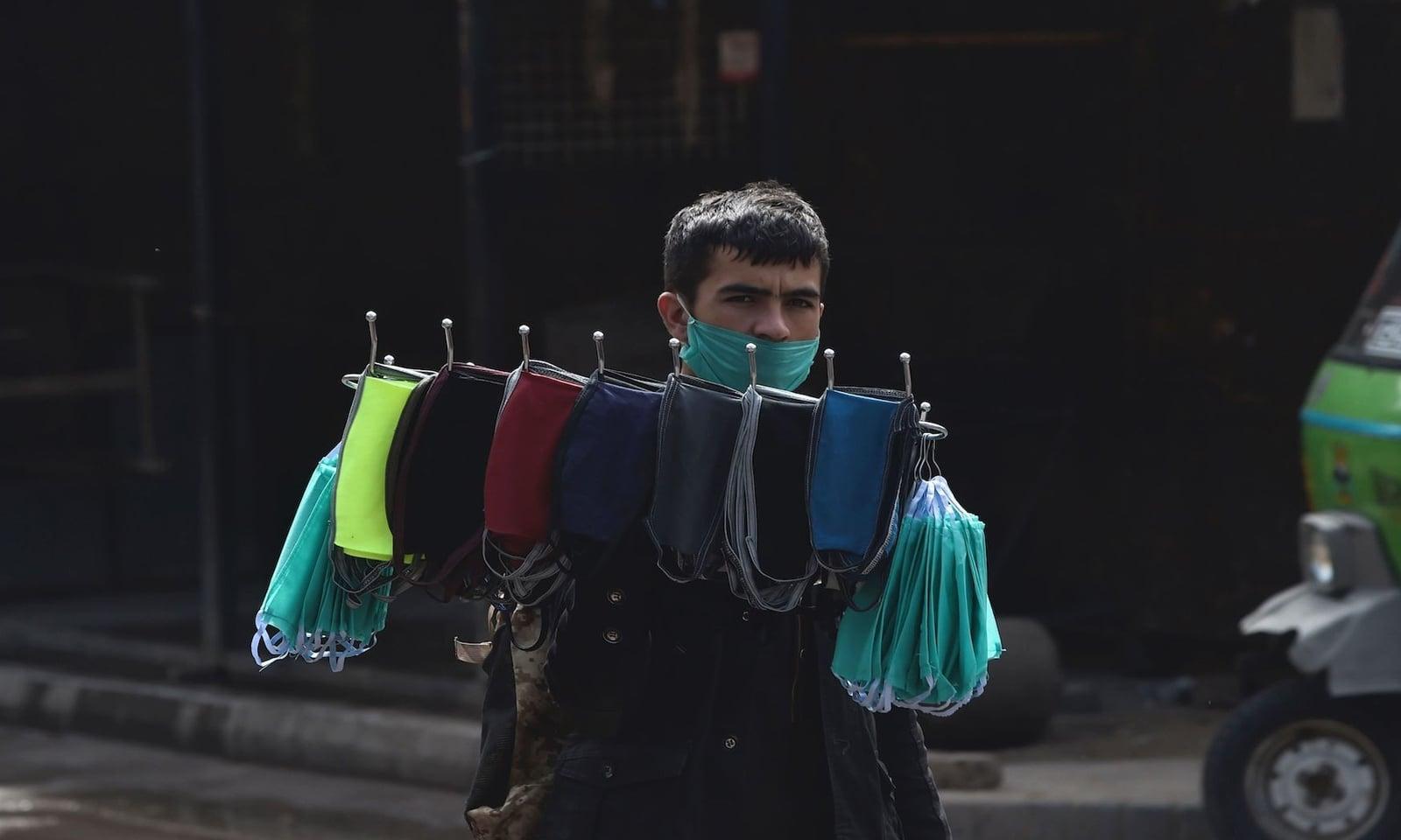 لاہور کی سنسان سڑک پر ایک شخص ماسک فروخت کرنے کی کوشش کر رہا ہے — فوٹو: اے ایف پی
