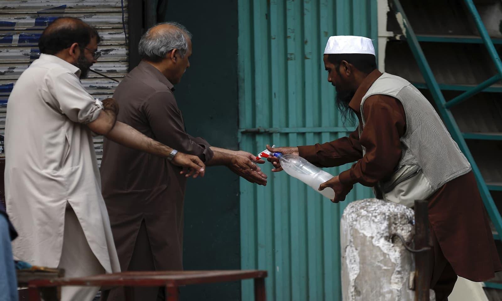 راولپنڈی میں ایک رضا کار نمازیوں کے ہاتھوں پر جراثیم کش اسپرے کر رہا ہے — فوٹو: اے پی