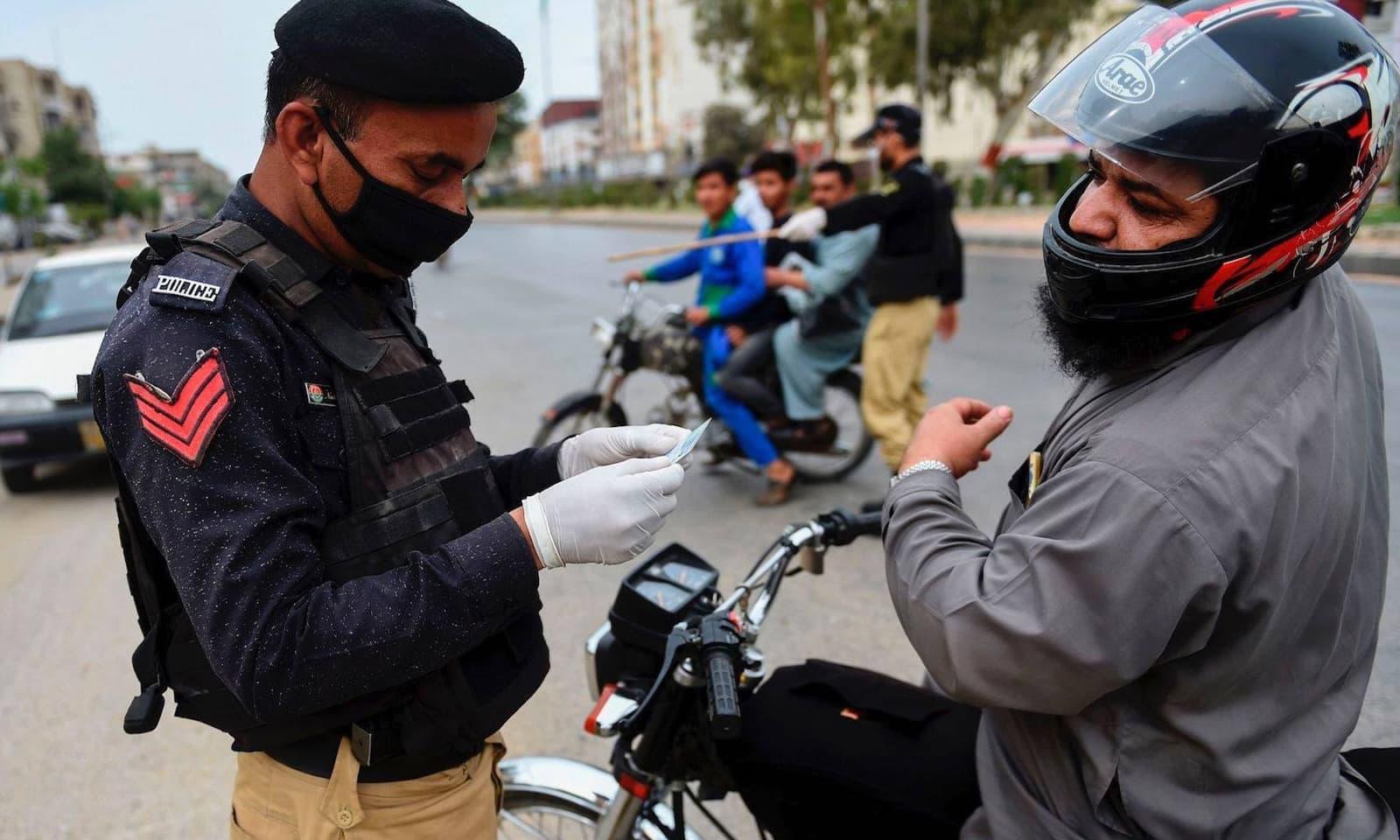 کراچی میں پولیس اہلکار موٹر سائیکل سوار کا شناختی کارڈ چیک کر رہا ہے — فوٹو: اے ایف پی