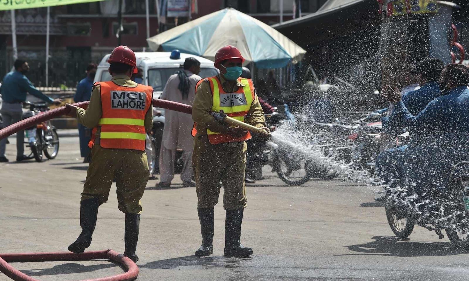 لاہور میں میونسپل کا عملہ جراثیم کش اسپرے کر رہا ہے — فوٹو: اے ایف پی