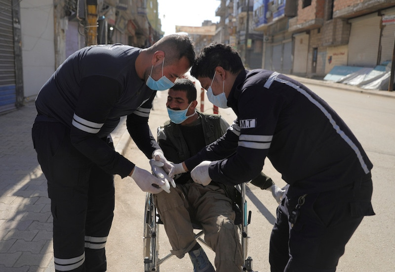 Health workers put gloves on a man in a wheelchair along an empty street, as restrictions are imposed as measure to prevent the spread of the coronavirus disease in Qamishli, Syria, on March 23, 2020. — Reuters