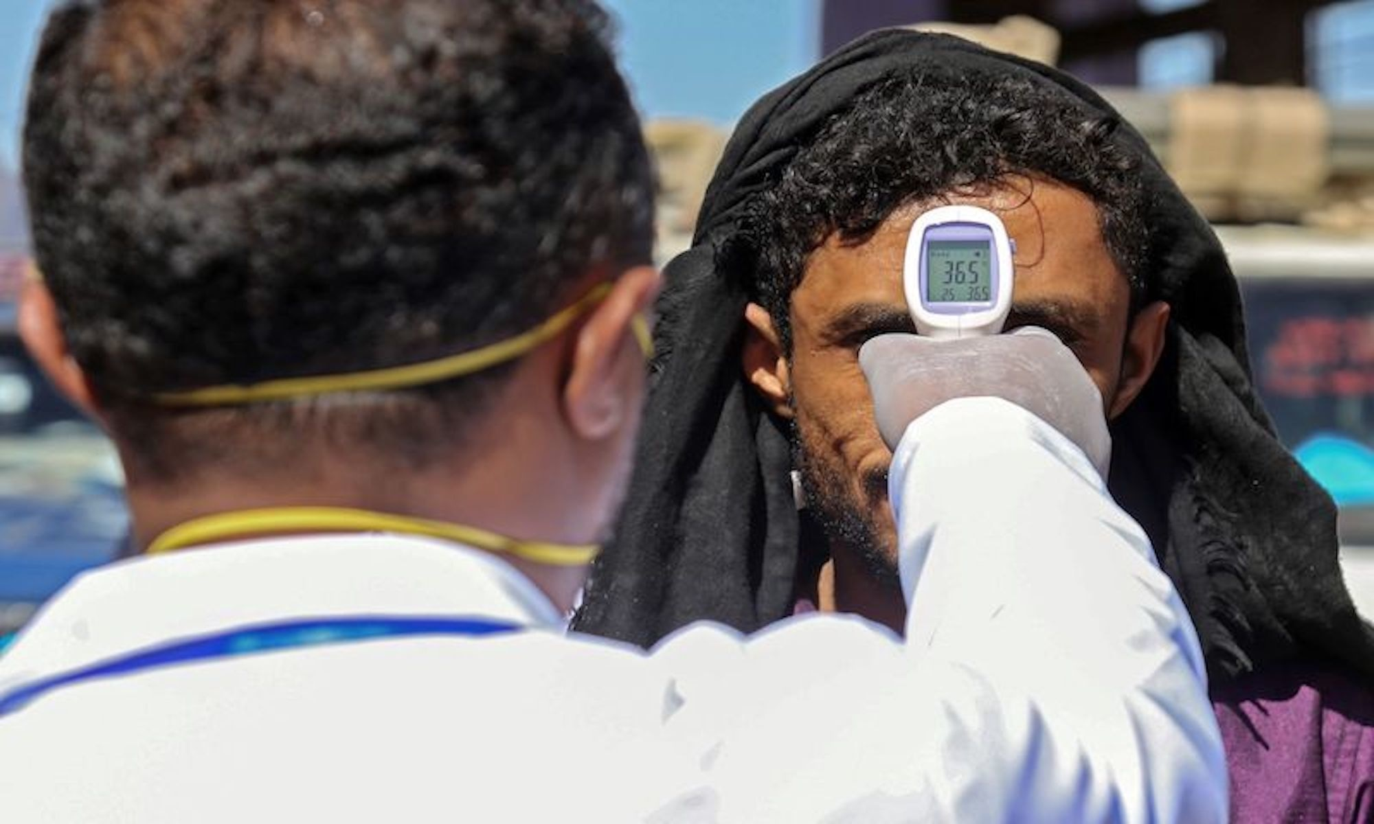A health official checks the body temperature of man at the entrance of the city of Taez in southwestern Yemen on March 23, 2020 amid concerns over the spread of the COVID-19 novel coronavirus. (Photo by Ahmad AL-BASHA / AFP) — AFP or licensors