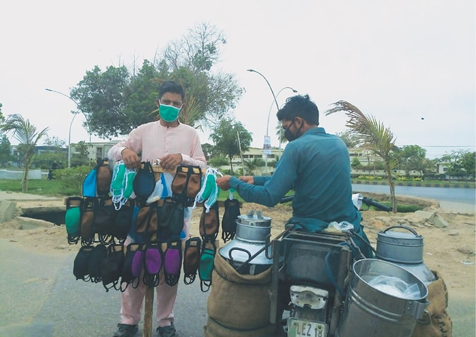 Noor Gul is approached by a milkman to buy a mask.—Photo by writer