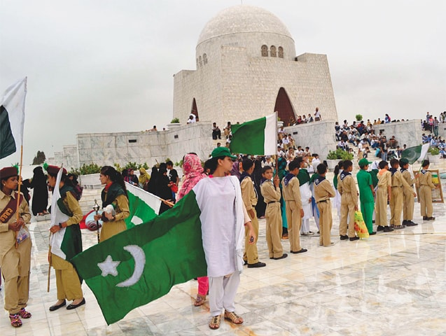 Kids hold up national flags at the Quaid's mausoleum during more normal times in this file photo.—White Star