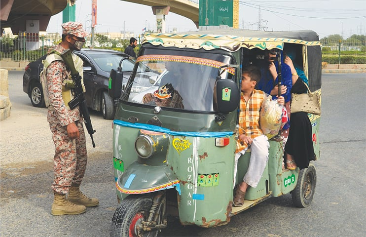 A LAW enforcer stops a rickshaw to admonish its driver and passengers for overloading on Monday. —White Star