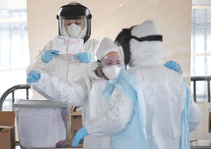 STAMFORD (Connecticut, US): Medical workers put on fresh personal protective equipment at a drive-thru coronavirus testing station.—AFP