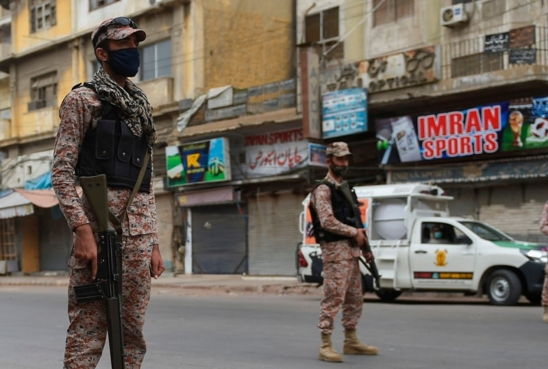 Soldiers wearing facevmasks stand guard on a deserted street during a lockdown after Sindh announced the closing of markets, public places and a ban on large gatherings amid concerns over the spread of the novel coronavirus in Karachi on March 23. — AFP
