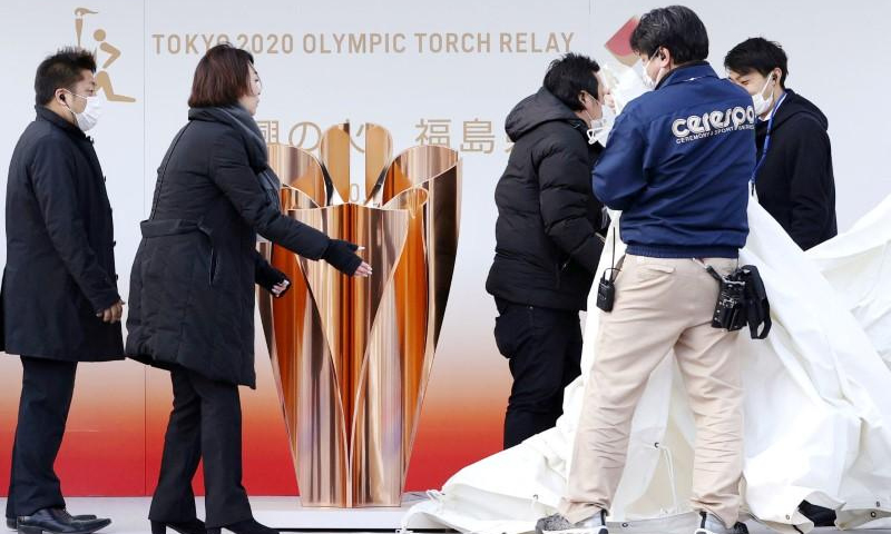 Officials remove the Olympic cauldron after the Tokyo 2020 Olympics Flame of Recovery in Fukushima, Japan on March 24. — Reuters