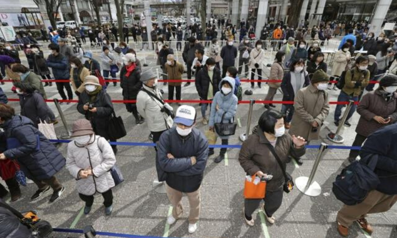 People, wearing masks, form a line while keeping distance from others as they try to watch the Olympic flame during the Tokyo 2020 Flame of Recovery in Fukushime, Japan. —Reuters