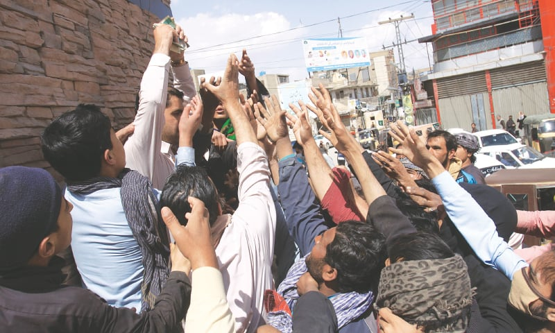 QUETTA: Daily-wage earners, who have almost become jobless due to the coronavirus outbreak, jostle with each other to lay their hands on money being distributed by a philanthropist on Tuesday.—AP