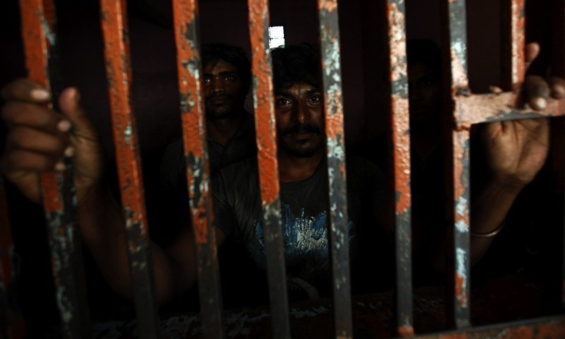 Fishermen from India stand behind bars in a lockup, after being detained in Pakistani waters, at a police station in Karachi April 18, 2015. According to local media, Pakistan maritime authorities arrested 47 Indian fishermen and took into custody their eight boats for illegal fishing in the country's territorial waters, police said on Saturday. REUTERS/Akhtar Soomro