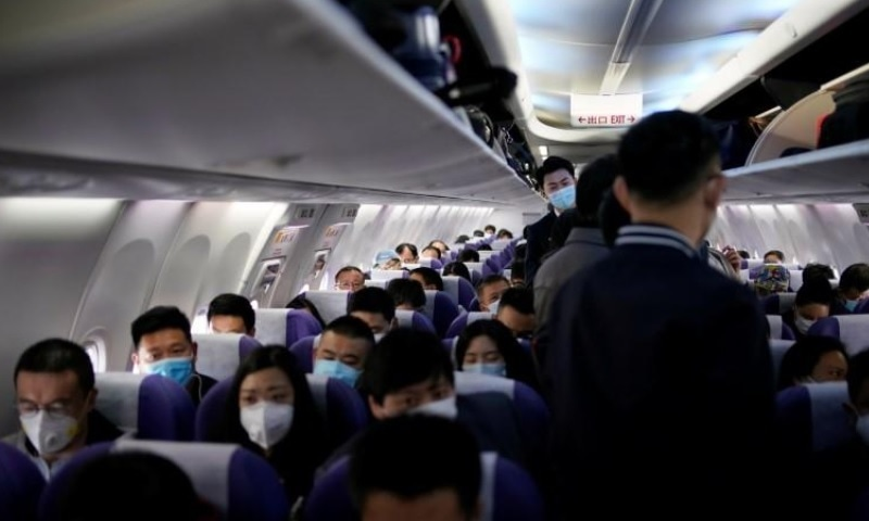 Passengers wearing face masks to prevent the spread of Covid-19 are seen on a Shanghai Airlines aircraft at Shanghai Hongqiao International Airport in Shanghai, China on March 25. — Reuters