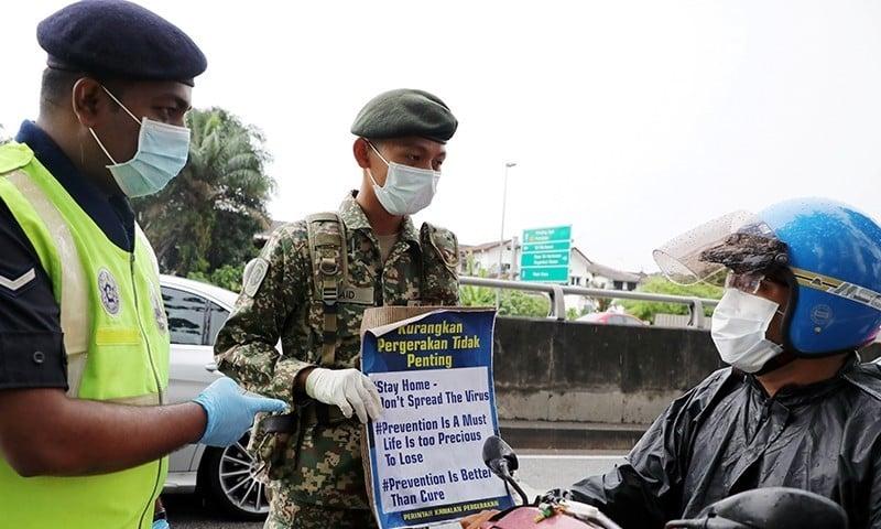 ملائیشیا میں سڑک پر موجود سیکیورٹی اہلکار ہاتھوں میں موجود پلے کارڈ کے ذریعے ایک موٹر سائیکل سوار پر ہدایات پہنچا رہے ہیں — فوٹو: رائٹرز
