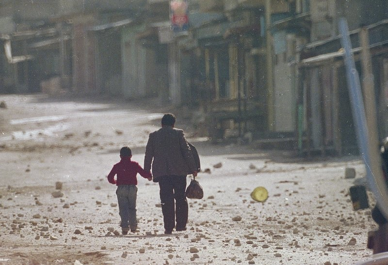 In this Dec. 11, 1987 file photo, a man holds his son's hand as they make their way along a debris littered street in the Balata refugee camp near Nablus in the occupied West Bank after a curfew was imposed on the camp. Western countries are reeling from the coronavirus pandemic, awakening to a new reality of economic collapse, overwhelmed hospitals and home confinement. But for millions across the Middle East and in conflict zones elsewhere, much of this is familiar — AP