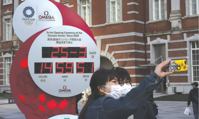 TWO WOMEN take a selfie with a Tokyo 2020 countdown clock displaying the current date and time outside Tokyo Station on Wednesday.—AP