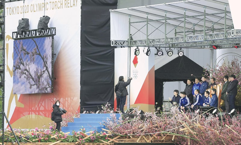 OFFICIALS take souvenir photos on Wednesday next to the Olympic cauldron as they start to remove the decorations at J-Village, a national football training centre in Naraha Town, Fukushima Prefecture, where the Olympic Torch Relay was supposed to start from.—Reuters