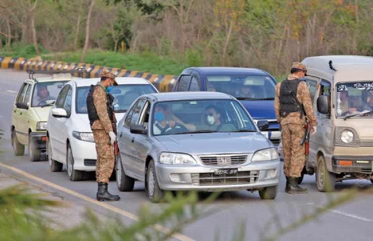 Army personnel check drivers before allowing them to proceed on Murree Road near Bhara Kahu in Islamabad on Wednesday. The area was sealed after detection of coronavirus cases. — Photo by Tanveer Shahzad