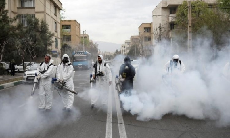 Firefighters wear protective face masks, amid fear of Covid-19, as they disinfect the streets, ahead of the Iranian New Year Nowruz, March 20, in Tehran, Iran on March 18. — Reuters