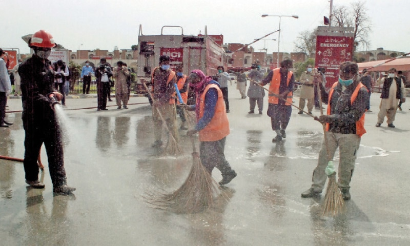 Municipal workers wash the Pims premises with chlorinated water as part of a disinfection campaign against the spread of Covid-19 on Thursday. — Photo by Mohammad Asim