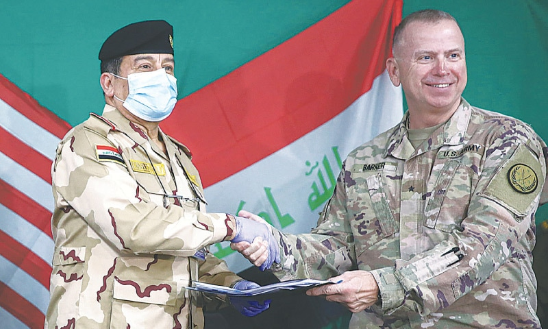QAYYARAH AIR BASE (Iraq): US-led coalition's Brigadier General Vincent Barker (right) and Major General Mohammad Fadhel Abbas of Iraq shake hands during a pullout ceremony on Thursday.—AFP