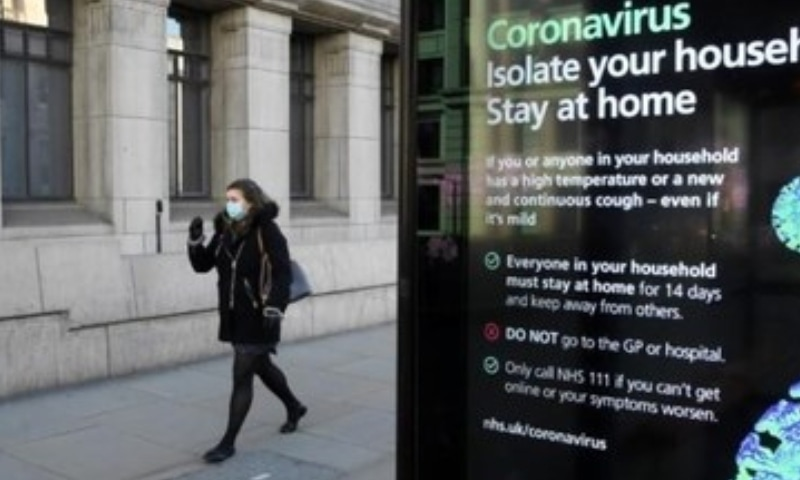 A woman wearing a mask is seen walking over London bridge with a coronavirus notice in the foreground, as the spread of the coronavirus disease continues, in London, Britain on March 23. — Reuters/File