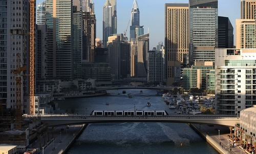 A tram crosses a bridge over a  canal that forms the Marina waterfront district of Dubai, United Arab Emirates. — AP