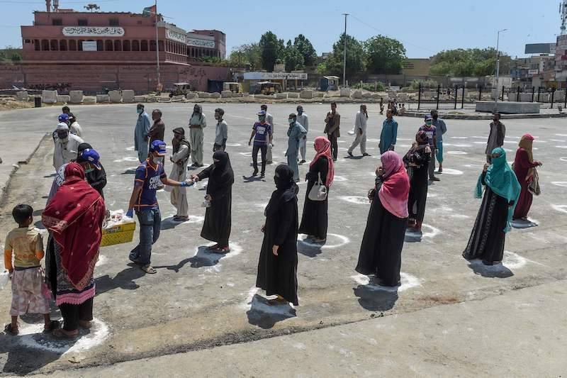 People stand in designated areas marked on the ground to maintain social distancing as they receive free food from volunteers of Chhipa Welfare Association during a government-imposed lockdown as a preventive measure against the coronavirus in Karachi on March 27, 2020. — AFP