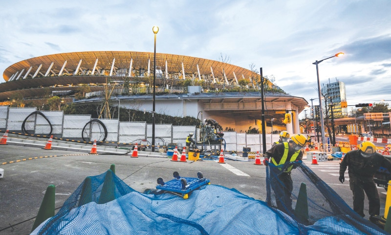 TOKYO: Labourers work on Friday at a site near the Japan National Stadium, the main venue for the Tokyo Olympics which have been postponed to 2021.—AFP