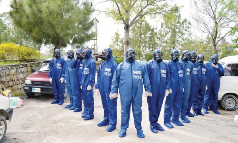 Police personnel in protective gear in Swabi. — Dawn