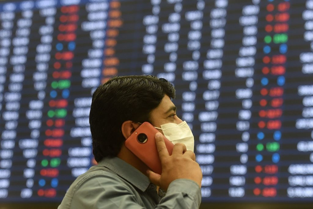 A stockbroker wearing a mask speaks on his cellphone as he watches share prices on a screen at the Pakistan Stock Exchange in Karachi | Asif Hassan, AFP