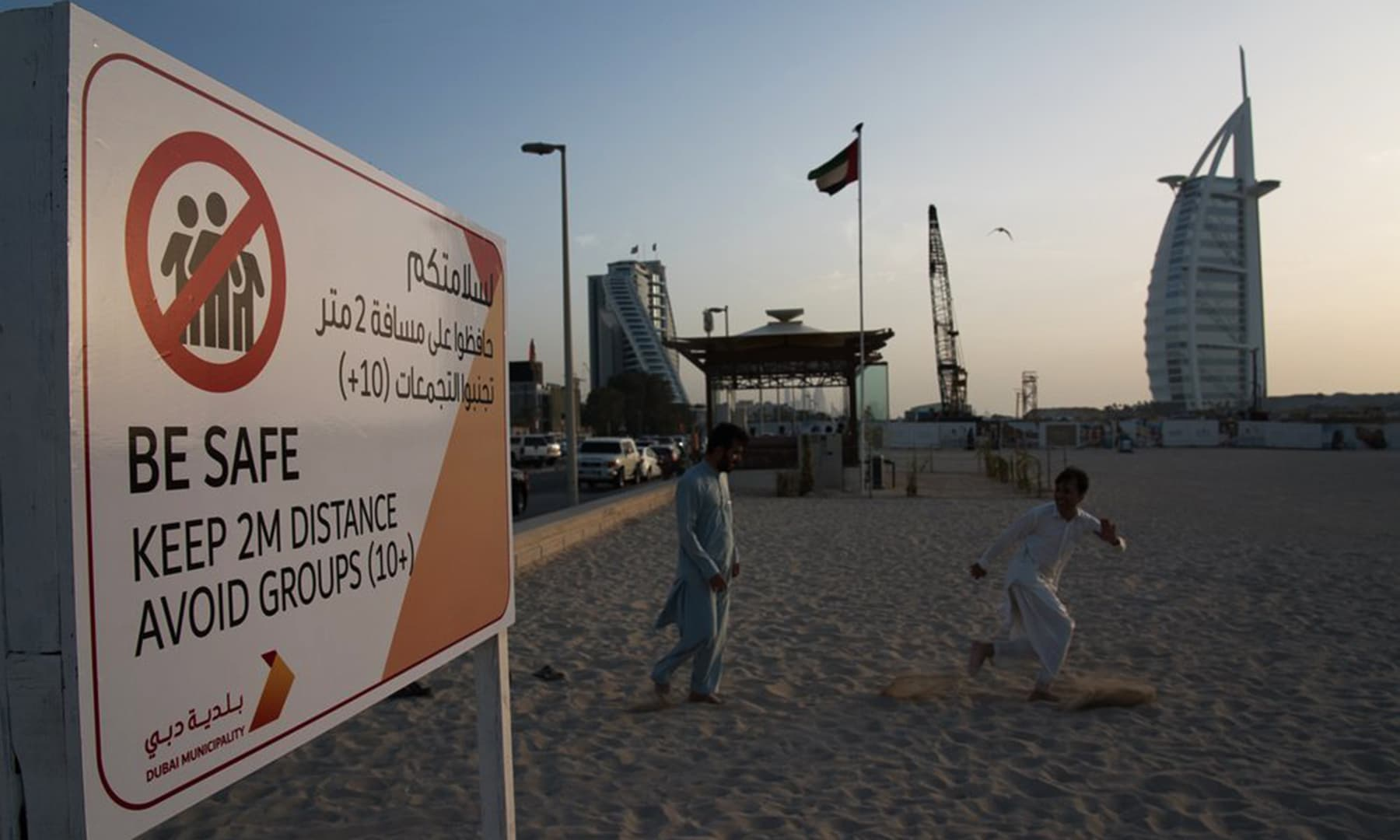 Two labourers play tag near a sign warning people to maintain a distance from each other over the outbreak of the new coronavirus in front of the sail-shaped Burj Al Arab luxury hotel in Dubai, United Arab Emirates. — AP